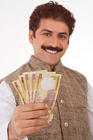 Man traditionally dressed holding indian currency