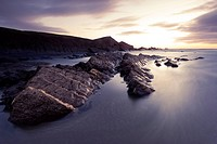 Long exposure of waves moving over rocks on Crackington Haven Beach at sunset, Cornwall, England, United Kingdom, Europe