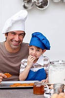 Father and son eating home_made cookies