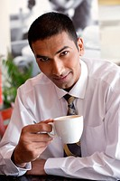 A young businessman having a cup of tea