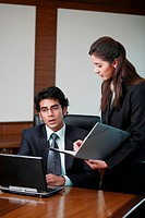 Businesswoman showing paperwork to businessman at desk