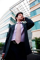 Businessman standing outside office building using mobile phone