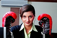 Businesswoman wearing boxing gloves, portrait