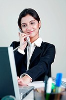 Businesswoman using laptop, talking on telephone