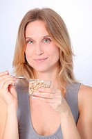 Closeup of beautiful blond woman eating cereals