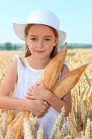 Closeup of little girl holding bread in wheat field
