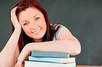 Close up of a smiling young student with her forearm on her book