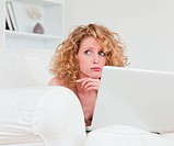 Lovely anxious female relaxing with her laptop while sitting on