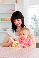 Beautiful brunette woman pealing a banana while holding her baby