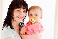 Attractive woman holding her baby in her arms while standing