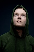 Portrait of hooded young man looking upwards