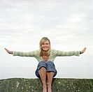 Blonde woman sitting on a stone