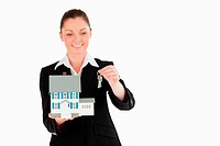 Charming woman in suit holding keys and a miniature house