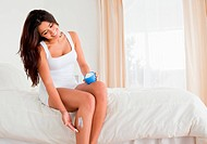 pretty woman putting creme on her legs while sitting on bed