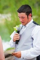 Young groom saying wedding vow to his bride at their outdoor wedding in Texas, USA