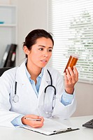 Beautiful worried doctor holding a box of pills