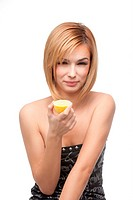 young woman tasting a lemon