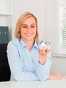 Gorgeous blonde businesswoman showing miniature house looking at