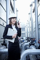 An architect in hardhat answering radio receiver, holding a report in her arm
