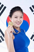 woman showing off a medal in front of the Korean national flag