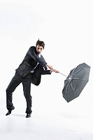 A man hit by the strong wind with an umbrella inside out