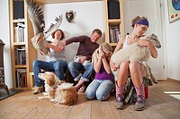 Family with fluttering goose and other animals at home