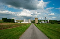 Dirt path leading to farm, with barns and silo in Maryland USA