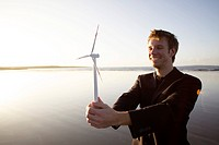 Man standing by the sea with wind engine