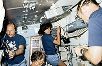Preparing food on space shuttle Challenger. Astronauts during mission STS_7 preparing food. At centre and bottom centre Sally Ride and Norman Thargard...