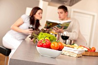 Couple in kitchen choosing recipe from cookbook