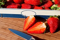 Fresh red Strawberries in a box with a knife