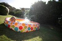 Girl in backyard paddling pool