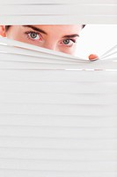 Businesswoman peeking through a venetian blind