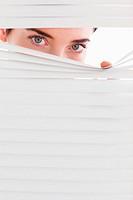 Businesswoman peeking through a venetian blind
