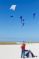 Woman flying kite with a Dali style clock face on St  Pete Beach at the Treasure Island Kite Festival in Treasure Island, Florida