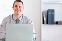Happy businessman working on his laptop