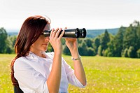 Businesswoman sit in sunny meadow seek binocular