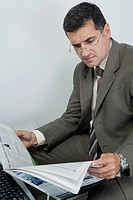 Businessman reading newspaper in office