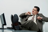 Businessman sitting in office with feet up on desk