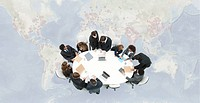 Business executives meeting on top of superimposed world map