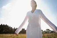 Mid_adult woman standing in field with eyes closed and arms outstretched