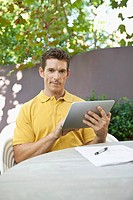 Man using digital tablet in garden (thumbnail)
