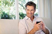 Man sitting on sofa using cell phone