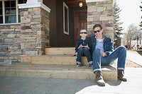 Dad and son sitting on front stairs of residence