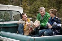 Three generations of males having lunch in back of truck