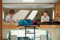 Siblings using computer technology in camper