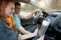 Young couple in car using pc tablet to navigate