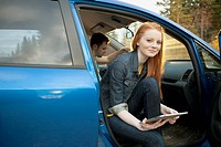 Pretty, young adult woman with pc tablet in car