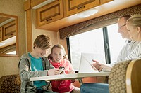 Family using computer technology in camper