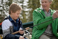 Grandfather assisting grandson with fishing gear